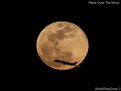 A plane flies in front of the Moon by worldtimezone
